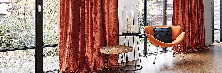 Fensterbereich mit Sitzgelegenheit und orangenen Vorhängen